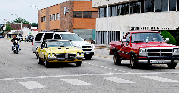 Traffic moves around an older model Pontiac Wednesday on west Broadway. The disabled car was left unattended in the eastbound lanes at the Washington intersection. (Staff Photo by BILLY HEFTON)
