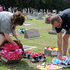 Marsha Harmon (left), from Moore, and Troy Harmon from Oklahoma City, decorate their family graves at Enid Cemetery Saturday, May 25, 2013. Even though Marsha Harmon's home was destroyed in the Moore tornado Monday, she paused to remember her loved one Memorial Day weekend. (Staff Photo by BONNIE VCULEK)