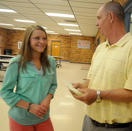 Peyton Isbell (left) a student at Waukomis High School, discusses the details of her Oklahoma anti-littering video with her instructor Phillip Pond in the school's gym lobby Wednesday, May 1, 2013. Isbell was the state high school art contest winner. (Staff Photo by BONNIE VCULEK)