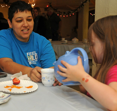 Raylee Blalock (right) pours a cup of tea for her mother, Kristin Mosqueda, during Applewood Early Learning Center's Mother's Day Tea Friday, May 10, 2013. (Staff Photo by BONNIE VCULEK)