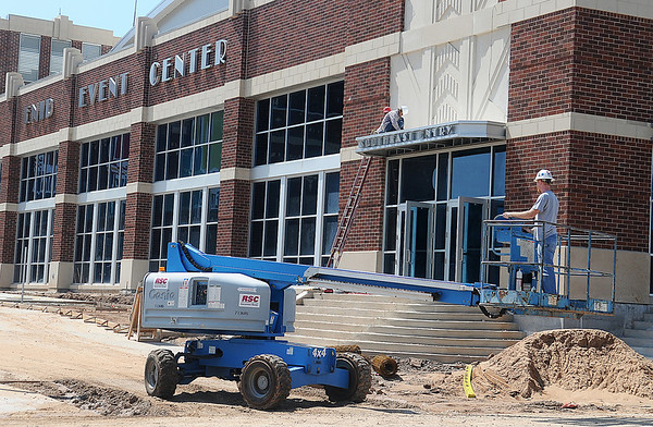 Enid Event Center lettering appears on the exterior of the new facility as painters put some finishing touches on the building Thursday, May 30, 2013. (Staff Photo by BONNIE VCULEK)
