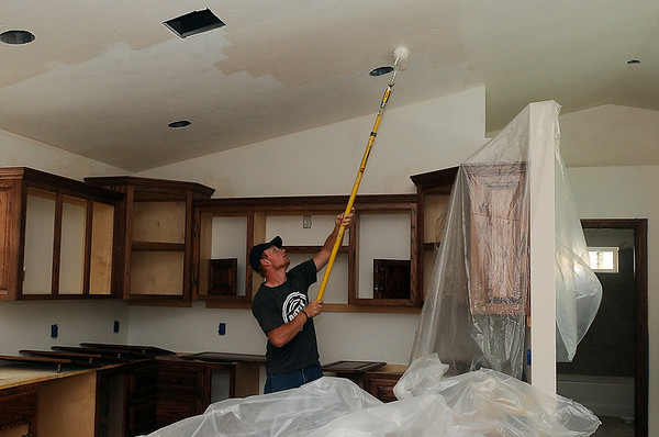 Cody Day, a first year adult student in Autry Technology Center's construction class rolls modest white paint onto the vaulted ceiling in the newest of ten home built at Autry. The 3-bedroom, 2-bath home with an open living-dining-kitchen features an open concept living-dining-kitchen with vaulted ceilings, red mahogany kitchen cabinets, pvc flooring, tiled showers, utility, a master bedroom walk-in closet, and plenty of extra storage. According to instructor Jeff Clark, high school and adult students should complete the interior work by Thursday, May 23. (Staff Photo by BONNIE VCULEK)