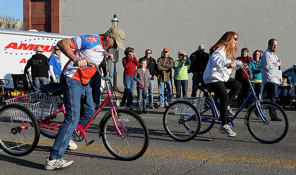 Cindy McFarland (right), with the Downtown Enid AMBUCS, takes an early lead over Jim Crabbs during the AMBUCS Tryke races at Main Street Enid's First Friday Jazz Stroll and Block Party May 3, 2013. (Staff Photo by BONNIE VCULEK)