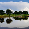 The clouds of a thunderstorm southeast of Enid are reflected on the water of Meadowlake Park. (Staff Photo by BILLY HEFTON)