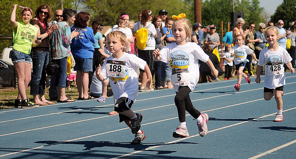 The crowd cheers as pre-kindergarten children near the finish line during the Be Fit Kids Buzz Run at Enid High School Saturday, May 11, 2013. More than 260 children participated in the event. (Staff Photo by BONNIE VCULEK)