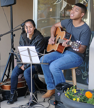 Jessica Navarro (left) listens as Gary Bangs performs in front of Laney's during the Tri-State Music Festival and Main Street Enid's First Friday Jazz Stroll May 3, 2013. (Staff Photo by BONNIE VCULEK)
