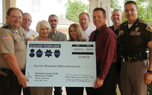 Carole Wade (front, second from left) accepts a check from command officials (clockwise, from left) Garfield County Sheriff Jerry Niles; Chaplain Butch Phillips, Under Sheriff  Jon Marshall, Kasey Bolton, Enid Police Capt. Bryan Skaggs, Enid Police Capt. Jack Morris; Oklahoma Highway Patrol Lt. Ken Jordan and Oklahoma Highway Patrol Capt. Brad Shepherd aat the Garfield County Child Advocacy Center; Members of the Vance 71st Security Forces Squadron, Garfield County Sheriff Department, Oklahoma Highway Patrol and Enid Police Department combined their efforts to raise $1,000 for the advocacy center during National Police Week. (Staff Photo by BONNIE VCULEK)