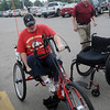 Gerald Blevins (right) watches as Jennifer Holmes transfers herself from her wheelchair to her new AmTryke for the first time at Jumbo Foods Saturday, May 18, 2013. Blevins made a donation to AMBUCS for the special AmTryke for Holmes, a Marine Veteran who was injured in a car crash in 2009. (Staff Photo by BONNIE VCULEK)