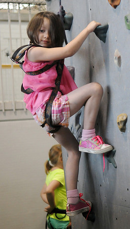 Nevaeh Williams looks toward her dad for reassurance during her first rock wall climb at the Denny Price Family YMCA Date With Dad Saturday, May 18, 2013. (Staff Photo by BONNIE VCULEK)