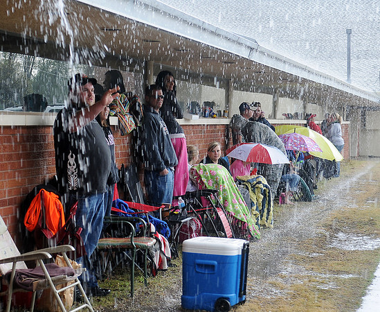 As heavy rain falls, parents wait to enroll their pre-kindergarten children outside Chisholm Elementary School Wednesday, May 1, 2013. The first parent arrived at 9:30 p.m. Tuesday evening to guarantee that her child would be one of the 40 students enrolled for the 2013-2014 school year. (Staff Photo by BONNIE VCULEK)