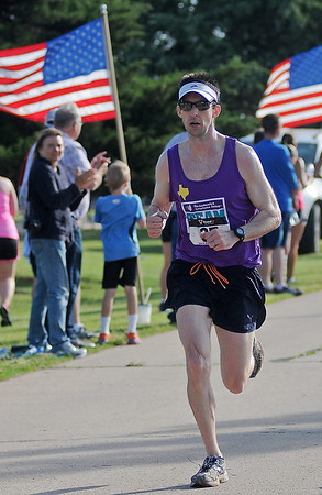 Adam Sandwick wins the Woodring Wall of Honor Red Dirt Run of Honor half marathon with a chip time of 1:34:08 at Enid Woodring Regional Airport Saturday, May 25, 2013. (Staff Photo by BONNIE VCULEK)