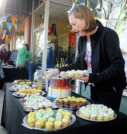 Vicki Brown serves free cupcakes to her guests during the T-Shirt Store's 35th anniversary party Friday, May 3, 2013. The festivities were part of the Tri-State Music Festival and Main Street Enid's First Friday Jazz Stroll. (Staff Photo by BONNIE VCULEK)