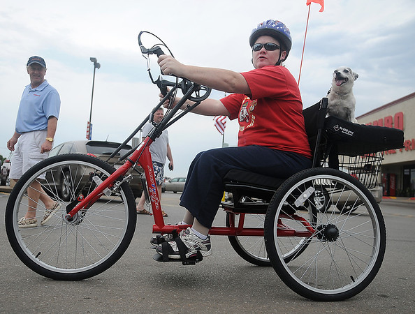 AMBUCS National President Kent Clingenpeel (Back Left), from Enid, watches Jennifer Holmes and her dog, Tater, ride her new AmTryke for the first time during the 3rd annual AMBUCS Crawfish Boil at Jumbo Foods Saturday, May 18, 2013. Gerald Blevins, owner of Jumbo Foods, provided funds for the special AmTryke for Holmes, while Clingenpeel made the final bike adjustments for her. Holmes, who served in the United States Marines from 1991-2001, was involved in a car wreck in 2009. Since then she has been confined to a wheel chair. (Staff Photo by BONNIE VCULEK)