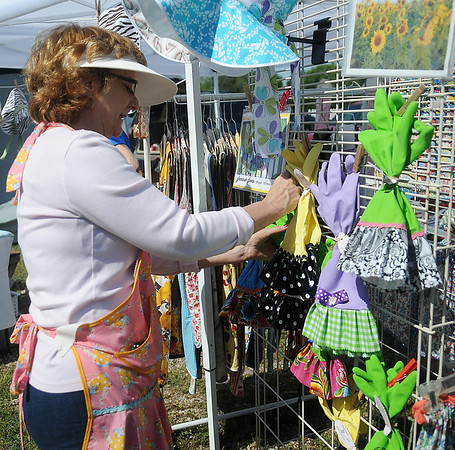 """Marcia Rogers, from Fairmont, arranges her glamour gloves at """"Kitchen Cuties"""" during Enid Farmers Market Saturday, May 11, 2013. Rogers creates home-sewn aprons, placemats, and several other items. (Staff Photo by BONNIE VCULEK)"""