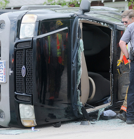 Reflections of Enid firefighters and Enid Police officers appear in the hood of an overturned Ford SUV at 624 S. Independence Friday, May 10, 2013. (Staff Photo by BONNIE VCULEK)