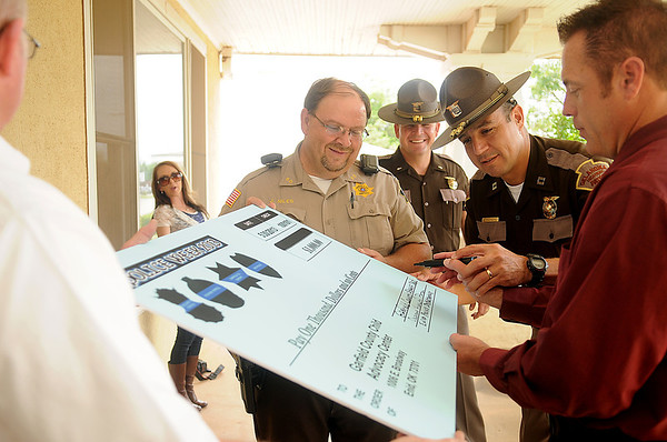 Butch Phillips (far left), Kasey Bolton (back left) and Oklahoma Highway Patrol Lt. Ken Jordan (back center) watch as Garfield County Sheriff Jerry Niles, Oklahoma Highway Patrol Capt. Brad Shepherd and Enid Police Department Captain Jack Morris sign a large $1,000 check for the Garfield County Child Advocacy Center during National Police Week Thursday, May 30, 2013. Members of the Vance Air Force Base 71st Security Forces Squadron, Garfield County Sheriff's Department, Oklahoma Highway Patrol and Enid Police Department combined their efforts to raise the funds. (Staff Photo by BONNIE VCULEK)