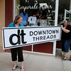 Vicki Brown and Manda Munger carry their new business sign out of The T-Shirt Store Wednesday, May 29, 2013. Brown has officially changed the name of her Enid business to align better with her clients requests. (Staff Photo by BONNIE VCULEK)