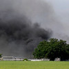 Smoke billows from a barn on south Oakwood Sunday as units of the Enid Fire Department work to contain the fire. (Staff Photo by BILLY HEFTON)