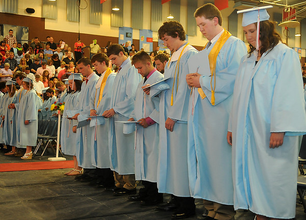 Chisholm High School graduating seniors bow their heads for the invocation by Class President, Alix Tyson, during the Longhorns' Commencement in the Paul J. Outhier Field House Friday, May 10, 2013. (Staff Photo by BONNIE VCULEK)
