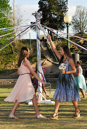 Enid High School female students wrap a may pole during the annual May Fete ceremony at Government Springs Park Tuesday. (Staff Photo by BILLY HEFTON)