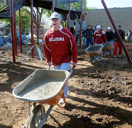 Craig Box (left) pushes a wheel barrow of mixed concrete during the community build at the new Champion Park Saturday, May 4, 2013. The workday, sponsored by the Austin Box Foundation, ran from 9 a.m.-3 p.m. at 10th and Chestnut, the former location of Wilson Elementary School. Austin Box, who was a star athlete at Enid High School and the University of Oklahoma football team, died May 19, 2011, of an overdose of painkillers. The new park was designed by Whitney Box, director of strategic and long-range planning for Enid. (Staff Photo by BONNIE VCULEK)