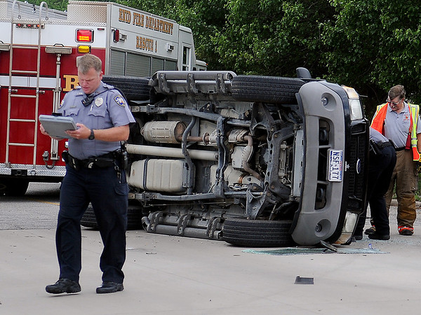 Enid Police officers and Enid Fire Department work a roll-over accident scene at 624 S. Independence Friday, May 10, 2013. (Staff Photo by BONNIE VCULEK)