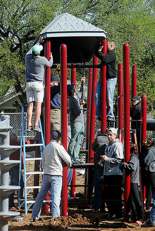 Community volunteers assemble playground equipment at the new Champion Park Saturday, May 4, 2013. The workday at 10th and Chestnut, the former location of Wilson Elementary School, was sponsored by the Austin Box Foundation. Austin Box, who was a star athlete at Enid High School and the University of Oklahoma football team, died May 19, 2011, of an overdose of painkillers. The new park designed by Whitney Box, director of strategic and long-range planning for Enid, will be an athletic park to get kids moving and more active. (Staff Photo by BONNIE VCULEK)