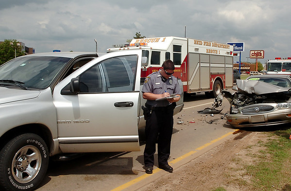 An Enid police officer gathers information from the vehicles involved in an accident on west Garriott Wednesday. (Staff Photo by BILLY HEFTON)