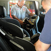 Lt. Steve Bartley and Lt. Shawn Kuehn, with the Enid Fire Department, properly install car seats during the Safe Kids Oklahoma car seat safety checks at the Enid Fire Department central station Wednesday, May 22, 2013. (Staff Photo by BONNIE VCULEK)