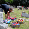 Troy Harmon (left), from Oklahoma City, and Marsha Harmon (right), from Moore, decorate the Harmon family gravesides in the Enid Cemetery Saturday, May 26, 2013. Troy Harmon promised his mother that he would carry on the Memorial  Day responsibility after her death. Even though Marsha Harmon's home in Moore was destroyed during Monday's tornado, she paused to remember her loved ones interred in Enid. (Staff Photo by BONNIE VCULEK)