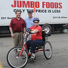 Gerald Blevins and Kent Clingenpeel pause for a portrait with Marine Veteran Jennifer Holmes and her puppy, Tater, during the AMBUCS 3rd annual crawfish boil at Jumbo Foods. Blevins furnished the funds to purchase the new AmTryke for Holmes who was injured in a car crash in 2009. Clingenpeel, the AMBUCS National President, made the necessary adjustments to the AmTryke for Homes and gave her a brief riding directions. (Staff Photo by BONNIE VCULEK)