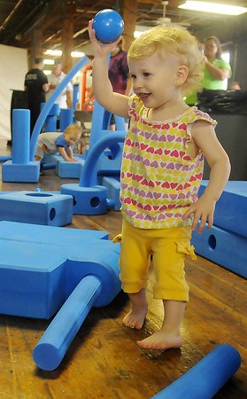 Rylee Gillespie, 2, uses a ball as she plays among the imagination playground pieces during the Children's Mental Health day at Leonardo's Discovery Warehouse Saturday, May 18, 2013. (Staff Photo by BONNIE VCULEK)