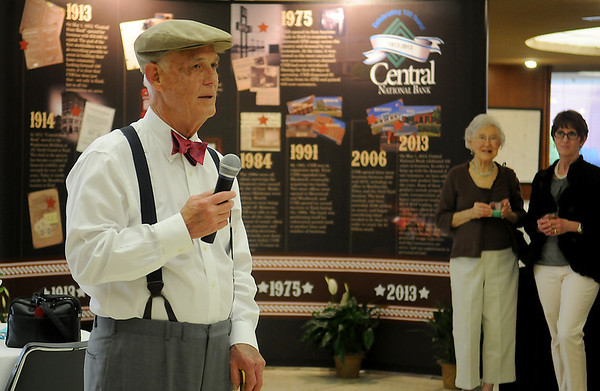Central National Bank President, Brud Baker, welcomes guests to the bank's 100th birthday celebration Wednesday, May 1, 2013. Baker was dressed as a newspaper delivery boy during the event. (Staff Photo by BONNIE VCULEK)
