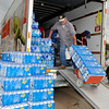 John Bingham pulls a hand cart full of bottled water in a U-Haul truck Tuesday. The water and other items were donated to the Moore tornado relief effort. (Staff Photo by BILLY HEFTON)