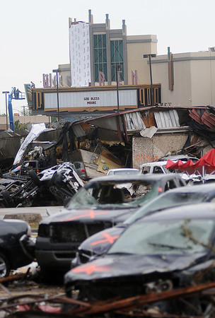 """The Warren Theatre marquee reads """"GOD BLESS MOORE"""" as tornado ravaged vehicles cover the edge of the theatre's parking lot in Moore, Okla. Tuesday, May 21, 2013. (Staff Photo by BONNIE VCULEK)"""