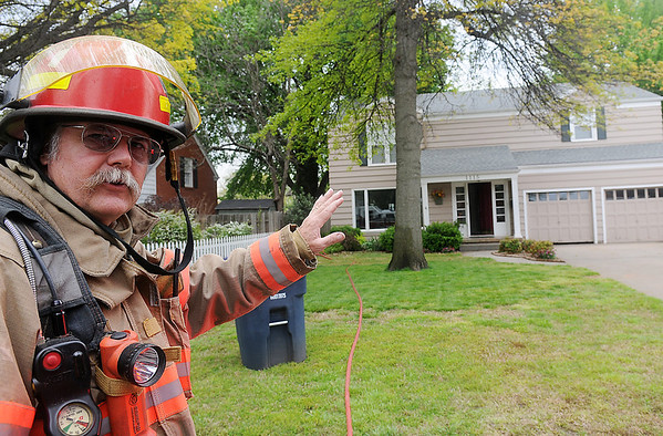Enid Fire Department Captain, Harvey Lenard, shares information about a small fire behind a residence at 1115 W. York Tuesday, May 7, 2013. (Staff Photo by BONNIE VCULEK)
