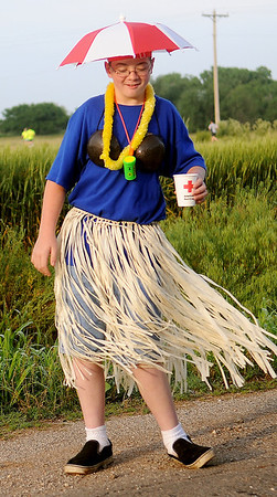 Jacob Gritz does the hula as he passes out water to the half marathon and 5K runners during the Woodring Wall of Honor Red Dirt Run of Honor Saturday, May 25, 2013. (Staff Photo by BONNIE VCULEK)
