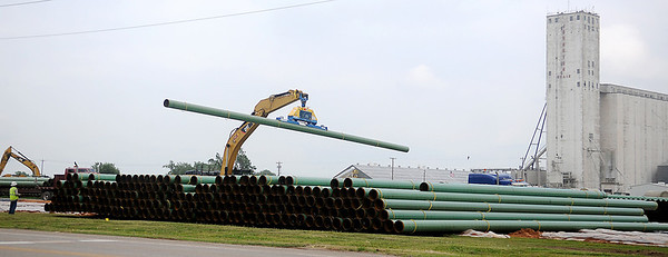 The blue cab of a semi-truck (right) is barely visible over transmission pipelines as a heavy equipment operator (left) unloads the sections of pipe near Johnston Enterprises on N. 30th Thursday, May 16, 2013. (Staff Photo by BONNIE VCULEK)