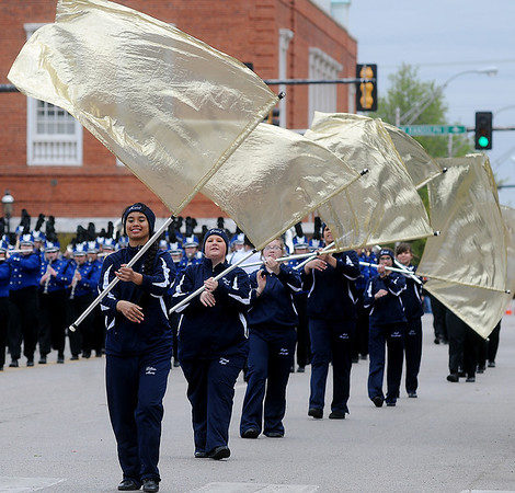 Enid High School Big Blue Band's flag corp members battle strong winds as they perform during the 81st annual Tri-State Million Dollar Parade Saturday, May 4, 2013. (Staff Photo by BONNIE VCULEK)