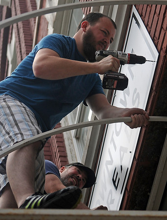 """Tyler Burge uses a hammer drill as he and John Trimmer install the new """"dt Downtown Threads"""" business sign above The T-Shirt Store Wednesday, May 29, 2013. Vicki Brown, owner of the local business, has changed the name to align better with her current client requests. (Staff Photo by BONNIE VCULEK)"""