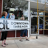 """Vicki Brown (left) and her daughter, Manda Munger, hold the new """"dt Downtown Threads"""" sign as employee, Tyler Burge, climbs the scaffolding to install the new business name above The T-Shirt Store Wednesday, May 29, 2013. Brown has changed the name, aligning more with her current clientele. (Staff Photo by BONNIE VCULEK)"""