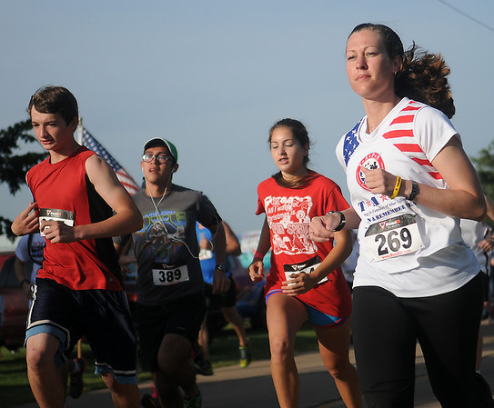 Karen Beattie (right), a gold star widow and Army soldier from Ft. Sill begins the 5K Woodring Wall of Honor Red Dirt Run of Honor Saturday, May 25, 2013. Beattie will hos a run in Qatar next year, a sister run to the one at Enid Woodring Regional Airport. (Staff Photo by BONNIE VCULEK)