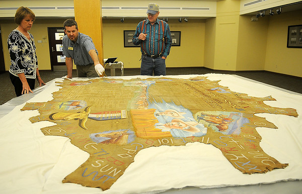 Andi Holland (left), executive director of the Cherokee Strip Regional Heritage Center, David Kennedy, the museum's curator of collections, and Albert Stehno, co-author of The Vanished Herd, examine a large buffalo hide Wednesday, May 8, 2013. The hide, donated to the Cherokee Strip Cow Punchers Association in the 1920s was designed and inscribed with members names from 1932-1934. The buffalo hide is now part of the museum's collection. (Staff Photo by BONNIE VCULEK)