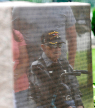 The image of World War II Navy veteran, Howard Poplin, is reflected in a stone of the Woodring Wall of Honor during Memorial Day ceremonies Monday. (Staff Photo by BILLY HEFTON)