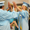 Chisholm High School seniors Ethan Kyle Petree and Kayla Ann Jantz (from left) high-five as they process in with their classmates during the CHS Graduating Class of 2013 Commencement in the Paul J. Outhier Field House Friday, May 10, 2013. (Staff Photo by BONNIE VCULEK)