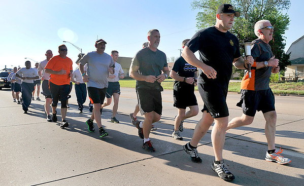 Members of the Enid Police Department, Garfield County Sheriff's Office, Oklahoma Highway Patrol and Vance Air Force Base Security Forces took part in a run Monday to kick off National Police Week. (Staff Photo by BILLY HEFTON)