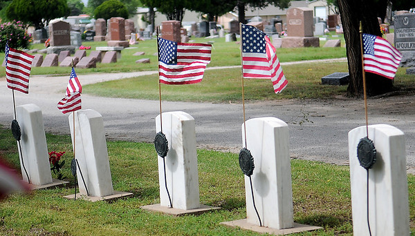 American flags mark the graves of Veterans at Enid Cemetery Saturday, May 25, 2013. Enid High School athletes placed the flags on the graves for Memorial Day. (Staff Photo by BONNIE VCULEK)