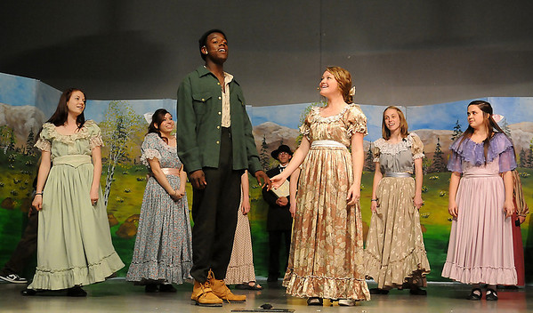 """Chris Walker, portrays Adam Pontipee (center, left) and Crystal Sawicki, plays Milly Bradon (center, right) as they rehearse a scene for Oklahoma Bible Academy's musical """"Seven Brides for Seven Brothers"""" Tuesday, May 7, 2013. The production, under the direction of Linda Zander, runs Friday-Sunday, May 10-12. (Staff Photo by BONNIE VCULEK)"""