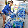 Terri Fletchall stacks a case of bottled water in a U-Haul truck Tuesday. The water and other items were donated to the Moore tornado relief effort. (Staff Photo by BILLY HEFTON)