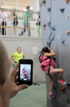 Steven Sharp videos his daughter, Nevaeh Williams, as she climbs the rock wall for the first time during the YMCA Date With Dad Saturday, May 18, 2013. (Staff Photo by BONNIE VCULEK)
